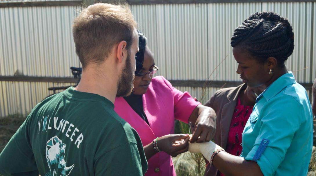 A Projects Abroad medical volunteer learns the correct way to put a bandage from a local doctor in Kenya.